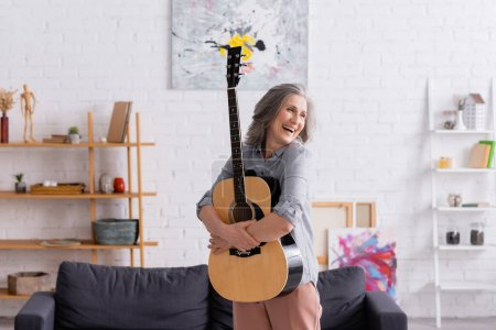 Photo for Cheerful mature woman with grey hair embracing acoustic guitar near couch in living room - Royalty Free Image