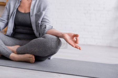 partial of mature woman sitting in lotus pose on yoga mat