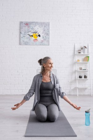 pleased mature woman with grey hair practicing yoga near sports bottle