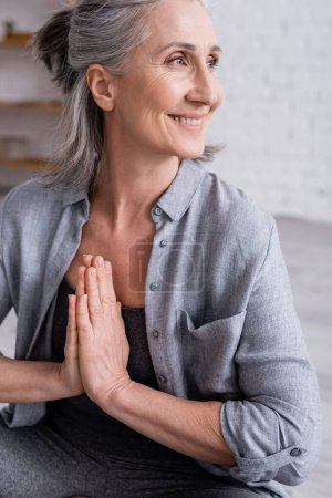 happy mature woman with grey hair and praying hands