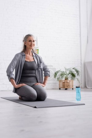 Photo for Happy mature woman with grey hair practicing yoga near sports bottle - Royalty Free Image