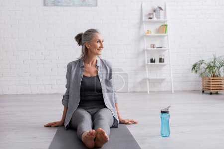 happy mature woman with grey hair sitting on yoga mat near sports bottle
