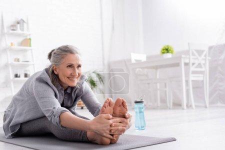 Photo pour Femme mûre gaie avec les cheveux gris étirant sur le tapis de yoga près de bouteille de sport - image libre de droit