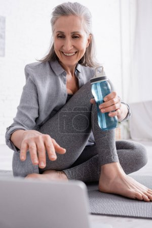 reife Frau sitzt auf Yogamatte und hält Sportflasche in der Hand, während sie Tutorial auf verschwommenem Laptop anschaut
