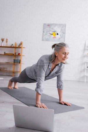 mature woman doing plank on fitness mat near laptop