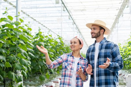 african american woman pointing at plants in glasshouse near smiling farmer