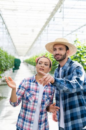 smiling farmer pointing with finger near african american colleague in glasshouse