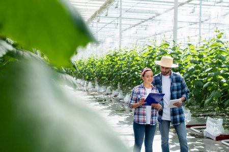 multiethnic farmers working with digital tablet and clipboard in greenhouse on blurred foreground