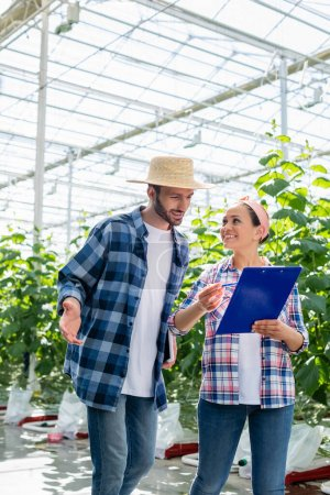 african american farmer pointing with pen at clipboard near colleague in glasshouse