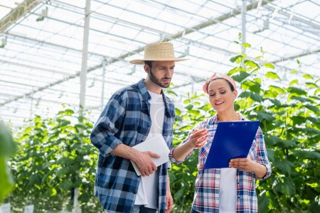 smiling african american farmer pointing at clipboard near colleague with digital tablet