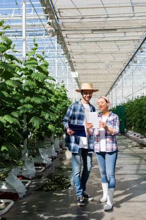 full length view of interracial farmers with clipboard and digital tablet near plants in glasshouse