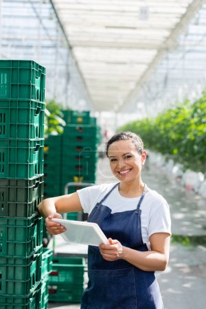 cheerful african american farmer standing with digital tablet near plastic boxes in greenhouse