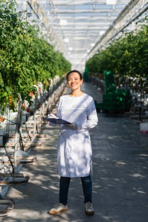 happy african american quality inspector standing with clipboard in greenhouse
