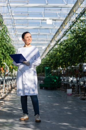 african american quality inspector looking away while standing in glasshouse with clipboard