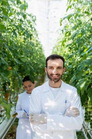 Photo pour Technologue agricole souriant regardant la caméra près d'un collègue afro-américain travaillant sur fond flou - image libre de droit