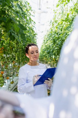 Photo for African american agricultural technologist writing results on clipboard on blurred foreground - Royalty Free Image