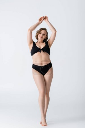 full length of overweight and barefoot young woman smiling while posing with raised hands on white