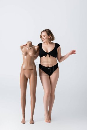 full length of overweight and smiling woman in swimsuit near plastic mannequin on white