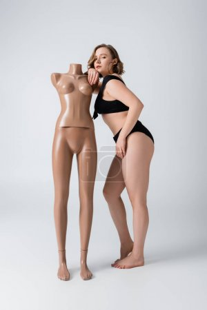 full length of overweight and barefoot woman in swimsuit leaning on plastic mannequin on white