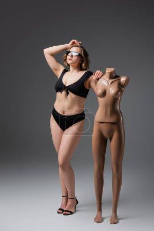 Photo pour Pleine longueur de jeune femme en surpoids dans des lunettes de soleil posant avec mannequin en plastique sur gris - image libre de droit