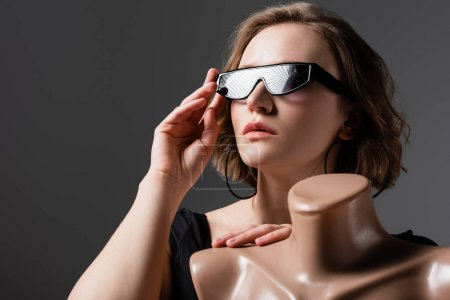 overweight young woman adjusting sunglasses and posing with plastic mannequin isolated on grey