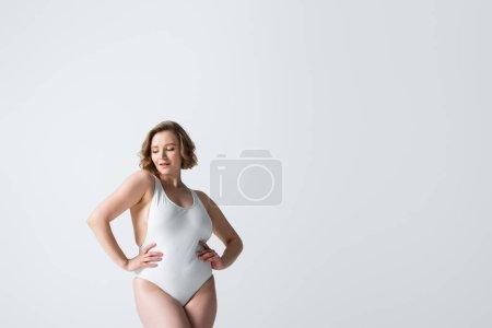 jeune femme en surpoids en maillot de bain posant avec les mains sur les hanches isolées sur blanc