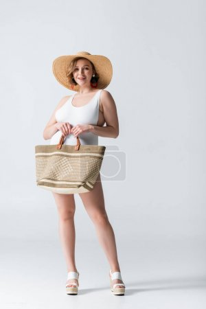 full length of overweight and happy woman in straw hat and swimsuit standing with bag on white
