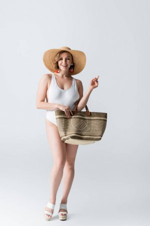 Photo for Full length of overweight and smiling woman in straw hat and swimsuit standing with bag on white - Royalty Free Image