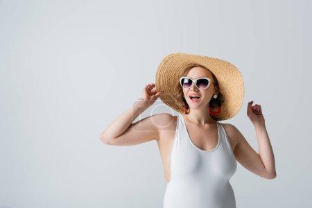 femme en surpoids et joyeuse en lunettes de soleil et maillot de bain réglage chapeau de paille isolé sur blanc