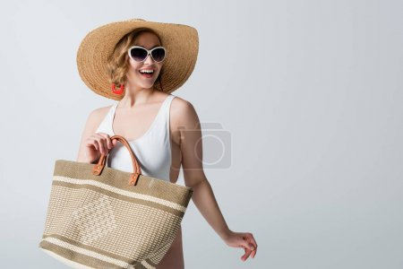 overweight and joyful woman in straw hat, sunglasses and swimsuit holding bag isolated on white