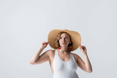 overweight and displeased woman in earrings and swimsuit adjusting straw hat isolated on white