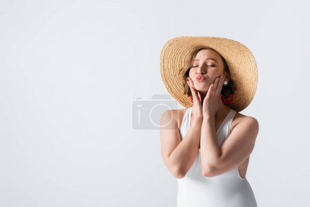 overweight young woman in earrings, swimsuit and straw hat pouting lips isolated on white