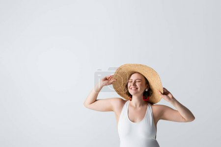 overweight and pleased woman in earrings and swimsuit adjusting straw hat isolated on white