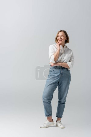 full length of happy overweight woman in jeans posing on grey