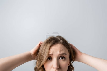 Photo for Cropped view of worried young woman looking at camera isolated on grey - Royalty Free Image