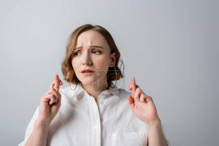 Photo pour Jeune femme en surpoids en chemise blanche avec les doigts croisés isolés sur gris - image libre de droit
