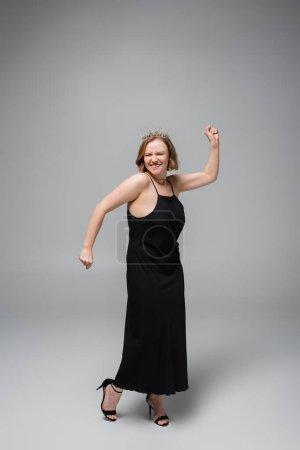 Photo pour Pleine longueur de femme heureuse plus la taille en robe de slip noir et couronne sur gris - image libre de droit