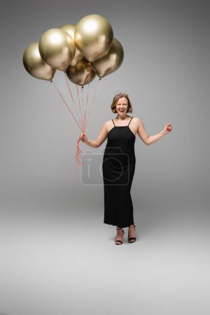 full length of excited plus size woman in black slip dress and crown holding golden balloons on grey