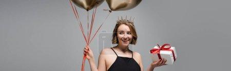 glückliche Plus-Size-Frau in Slip-Kleid und Krone mit goldenen Luftballons und Geschenk isoliert auf grau, Banner