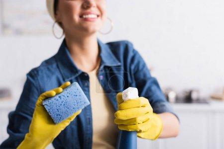 Cropped view of detergent and blurred sponge in hands of smiling woman