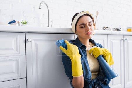 Photo pour Mauvaise femme au foyer dans des gants en caoutchouc tenant éponge et détergent dans la cuisine - image libre de droit