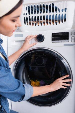 Photo pour Femme au foyer floue commutant la machine à laver près du panier avec des vêtements - image libre de droit