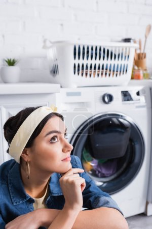 Photo for Dreamy housewife sitting near blurred washing machine in kitchen - Royalty Free Image