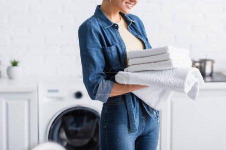 Photo pour Vue recadrée de la femme au foyer souriante tenant des serviettes propres - image libre de droit