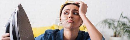 Triste femme au foyer tenant du fer flou à la maison, bannière