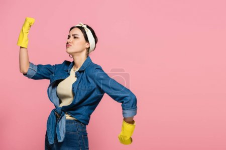Hausfrau in gelben Gummihandschuhen zeigt Muskeln isoliert auf rosa