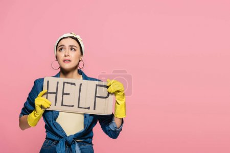 Young housewife in rubber gloves holding placard with help lettering isolated on pink