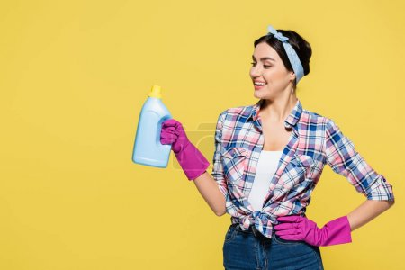 Smiling housewife holding bottle of detergent isolated on yellow