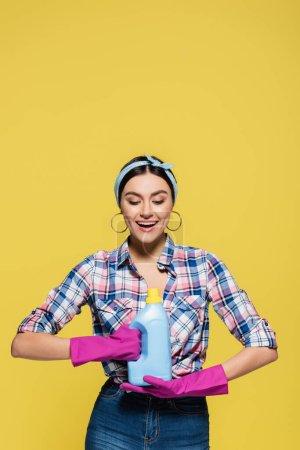 Photo pour Femme souriante en gants de caoutchouc regardant une bouteille de détergent isolée sur jaune - image libre de droit