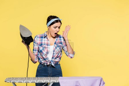 Worried woman holding iron near clothes on board isolated on yellow